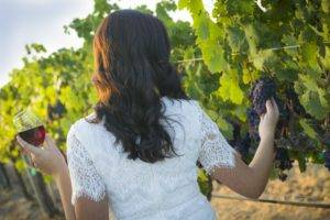 Woman-in-vineyard-looking-at-grapes-holding-wine-glass-300x200.jpg